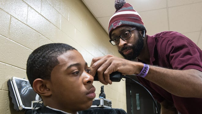 Woody Sharp trims the hair of Oyrne Stewart, of Concordia Preparatory School, at the Wicomico Youth and Civic Center on Wednesday, Dec. 27, 2017.