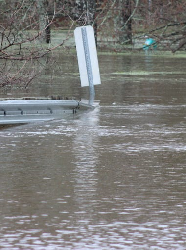 Water covers a bridge leading into Treasure Island subdivision in Monroe on Thursday.