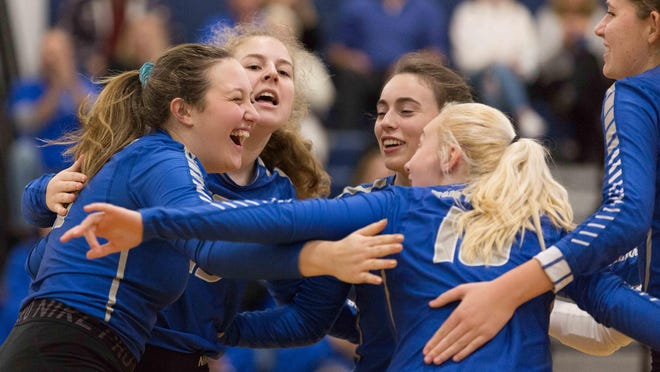 Members of the Lyman Memorial volleyball team celebrate a point during the 2019 Class S state championship game.