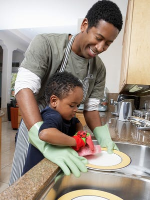 Father and son washing dishes.