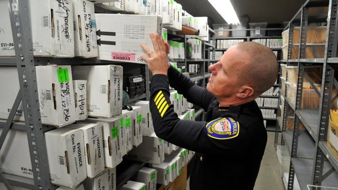 JOSEPH A. GARCIA/THE STAR Eric Sonstegard, assistant chief of police, looks over boxed guns in the Oxnard Police Department's property room that were collected as evidence.