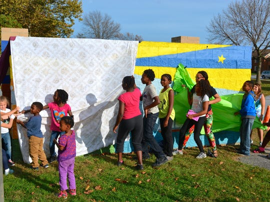 Children in the Burton Village community unveil a new mural painted in the community near Rehoboth Beach on Thursday, Oct. 29.