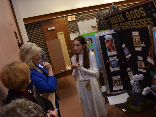 Hannah Winget (far right), a Scott M. Brame Middle School seventh-grader, talks about her project on Greek gods and goddesses to judges at the Rapides Parish Social Studies Fair held Thursday.