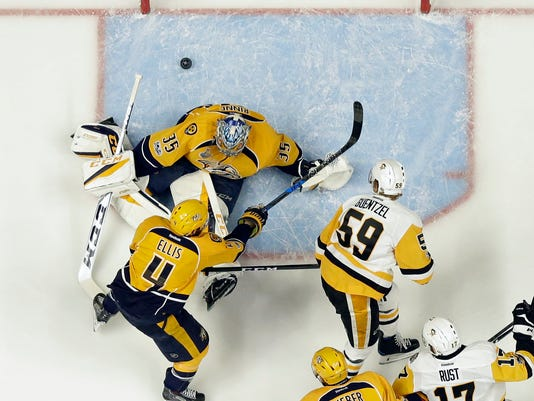 Pittsburgh Penguins center Jake Guentzel (59) shoots the puck past Nashville Predators goalie Pekka Rinne, of Finland, (35) and Ryan Ellis (4) for a goal during the first period of Game 3 of the NHL hockey Stanley Cup Finals Saturday, June 3, 2017, in Nashville, Tenn. (AP Photo/Mark Humphrey)