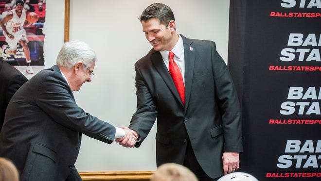 Mike Neu shakes president Paul Ferguson's hand during Neu's press conference at Worthen Arena Friday.