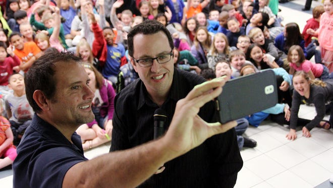 """Russ Taylor, then executive director of the Jared Foundation, left, and Jared Fogle, """"the subway guy,"""" pose to take a photo of themselves with the students of Euper Lane Elementary School in Fort Smith, in 2014, after speaking to the children about the dangers of childhood obesety."""