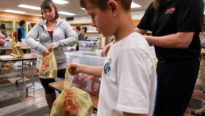 Volunteers gather items to be included in meals as part of the Rocori Action Packs program Tuesday, March 21, in Cold Spring.