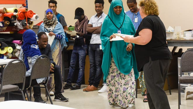 Students receive certificates for the completion of an adult education program Wednesday, Aug. 16, at the Coleman Co. Inc. in Sauk Rapids.