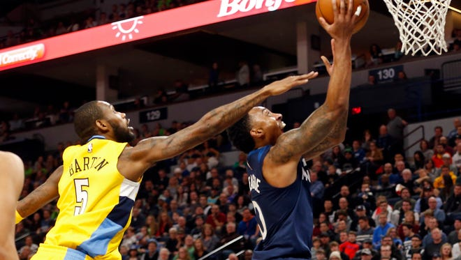 Minnesota Timberwolves' Jeff Teague, right, lays up as Denver Nuggets' Will Barton defends in the first half of an NBA basketball game Wednesday, Dec. 27, 2017, in Minneapolis. (AP Photo/Jim Mone)