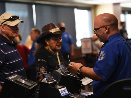 A TSA agent checks a traveler's identification document at the Reno-Tahoe International Airport in Reno. The TSA is one of several employers taking part in a Reno job fair on Oct. 17.