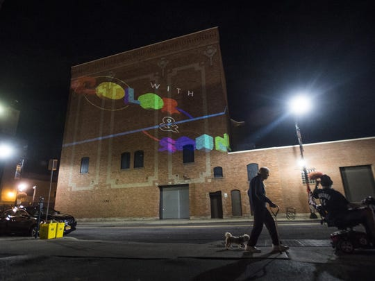 Pedestrians pass by a projected image along State Street in downtown Binghamton on Tuesday, August 25, 2015.