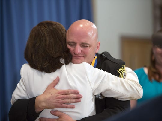 Johnson City police officer Louis Cioci hugs New York