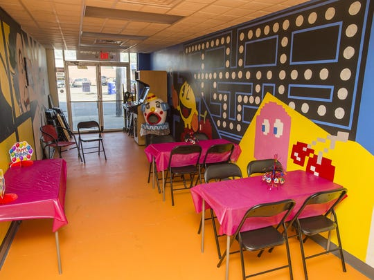 The walls of Warrior Games arcade in Hillcrest are painted with various classic video game characters like Pac Man.