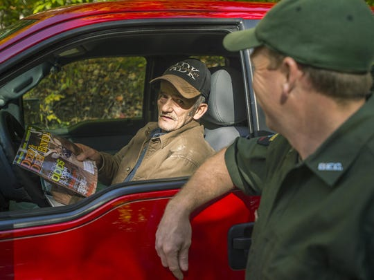 Dean Moulton, 64, a lifelong resident of Indian Lake, NY, hands forest ranger Jay Scott a pile of used hunting magazines while surveying the number of rafters traveling along Indian Lake. The two men have developed a friendly rapport as they both oversee rafting in the area.
