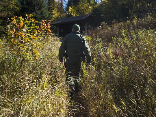 Ranger Scott walks through brush towards a lean-to along the far end of Indian Lake. There are a series of lean-to's throughout the Adirondack's that serve as shelter for hikers traveling long distances.