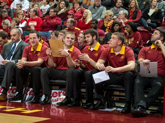 Iowa State managers sit on the bench during a college