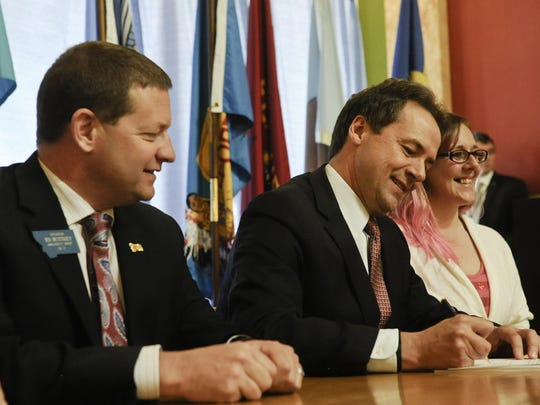 Democratic Gov. Steve Bullock, center, signs a bill April 29, 2015, to expand Medicaid as bill sponsor Republican state Sen. Ed Buttrey, R-Great Falls, looks on.