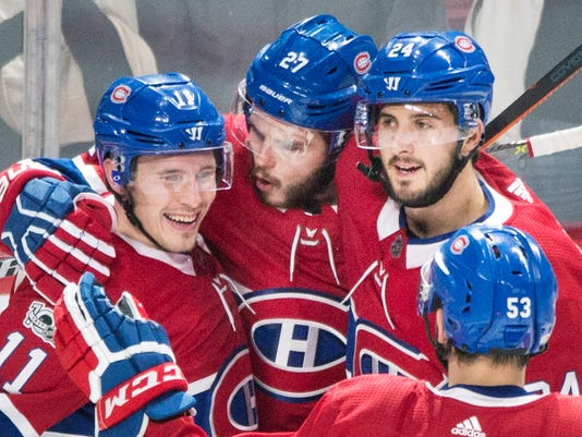 Montreal Canadiens' Alex Galchenyuk (27), celebrates with teammates Brendan Gallagher (11), Phillip Danault (24) and Victor Mete (53) after scoring against the New York Rangers during first-period NHL hockey game action in Montreal, Saturday, Oct. 28, 2017. (Graham Hughes/The Canadian Press via AP)