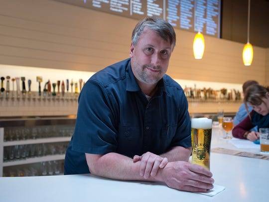 Owner Kevin Bolin poses at The Mayor of Old Town tap house in Fort Collins with a Pivo Pils by Firestone Walker Brewing Co.