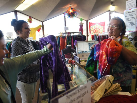 Lauren Hufft, right, owner of Prism Magic Clothing and Imports, sells some tie dye clothes to Melissa Manley, middle, and Michelle McKenzie at her store in Sparks on Jan. 8.