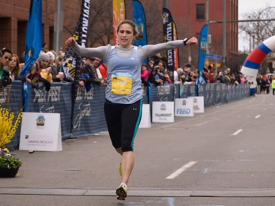 First place finisher for the women in the half marathon, Trisha Byler runs through the finish line with a time of 1:21:29, at the Flower City Challenge, Sunday, April 26, 2015.