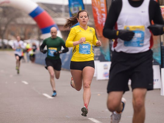 First place finisher for the women in the Wegmans Family 5K, Laura Anderson, crosses the finish line Sunday, April 26, 2015.
