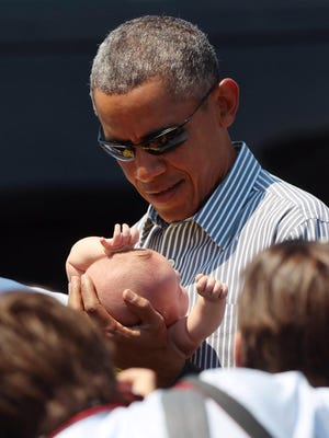 President Barack Obama holds Sky, the daughter of Rep. Raul Ruiz, during his fifth visit to the Coachella Valley.