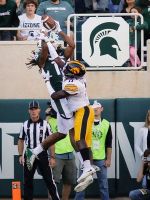 MSU receiver Felton Davis III snags a pass over Iowa's Michael Ojemudia for a second quarter touchdown Saturday at Spartan Stadium.