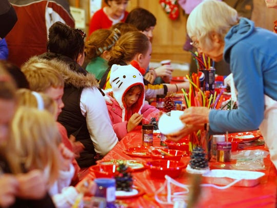 Children and adults make crafts in the Lodge during the 36th Annual Christmas Festival at Silver Falls State Park on Sunday., Dec. 15, 2013.