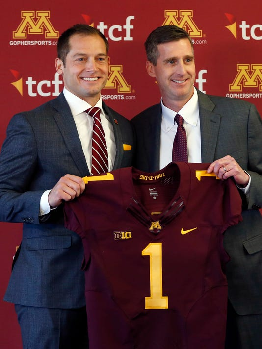 University of Minnesota athletic director Mark Coyle, right, introduces P.J. Fleck as the new head football coach during a news conference Friday, Jan. 6, 2017, in Minneapolis. (AP Photo/Jim Mone)