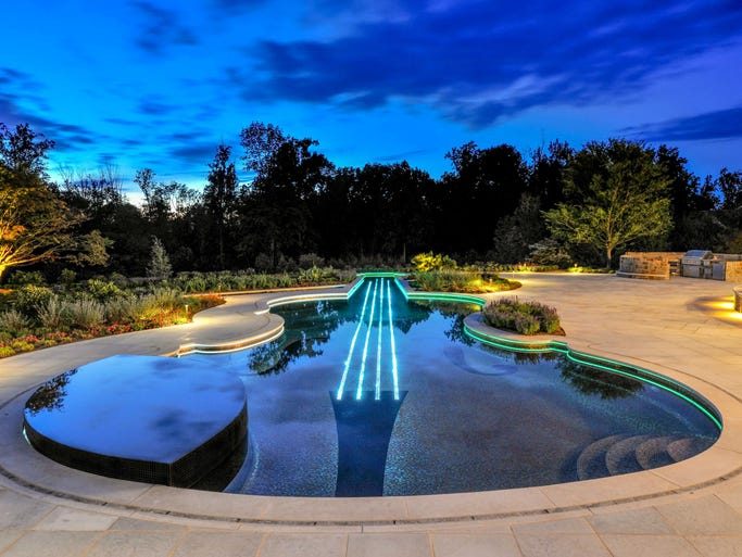 "This pool, shaped like a rare Stradivarius violin, was created by Cipriano Landscape Designs. Included in the pool's design are the F holes, the strings, the base and a chin rest that is actually a spa. ""It is a perimeter overflow hot tub; the water falls off the sides and on the patio,"" says Chris Cipriano. ""The water actually falls through the patio; there are channels for it."""