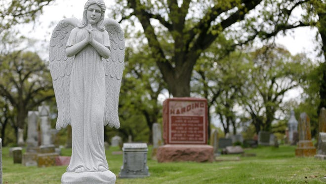 A series of angel statues watch over the graves in Des Moines' Woodland Cemetery.