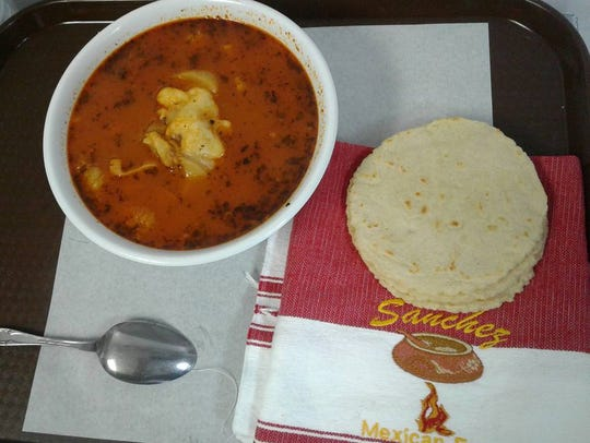 The traditional menudo soup, served with tortillas,