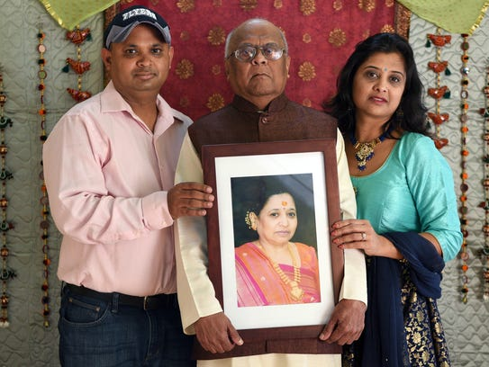 Kaushal and Neha with their father, Dharnedra Shah, hold a picture of Rekhaben Shah.