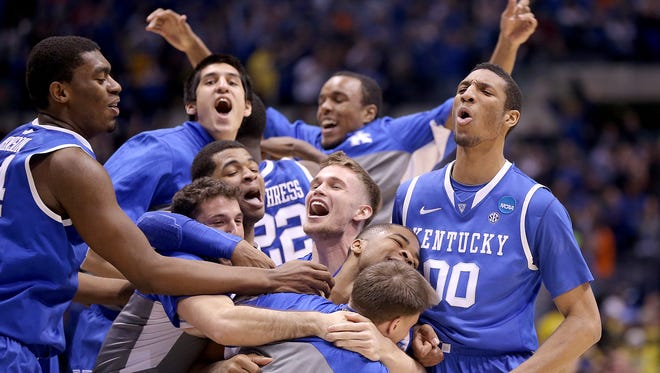 The Kentucky Wildcats celebrate their win over Michigan in the NCAA tournament's Midwest Regional championship game March 28, 2014, at Lucas Oil Stadium.
