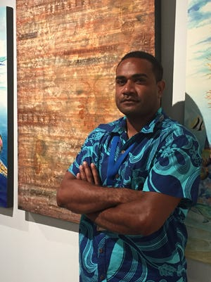 Fijian artist Waqa Vuidreketi stands next to his painting at the opening of the Festival of Pacific Arts Visual Arts exhibit at the Guam Museum on May 25.