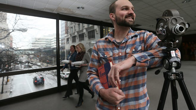 Iowa filmmaker Paul Benedict is shown on a sky walk in downtown Des Moines with a vintage camera that be longed to his grandfather.