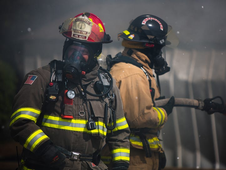 Delta Township firefighters put out the flames of a