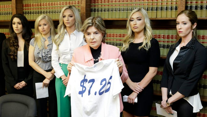 Attorney Gloria Allred stands among former Houston Texans cheerleaders, from left, Ashley Rodriguez, Morgan Wiederhold, Kelly Neuner, Hannah Turnbow, and Ainsley Parish, right, while holding up a shirt printed with $7.25, the amount she says the former cheerleaders where paid per hour, as she speaks during a press conference Friday, June 1, 2018, in Humble, Texas, announcing a lawsuit on behalf of the five the former cheerleaders at the law offices of Kimberley Spurlock.