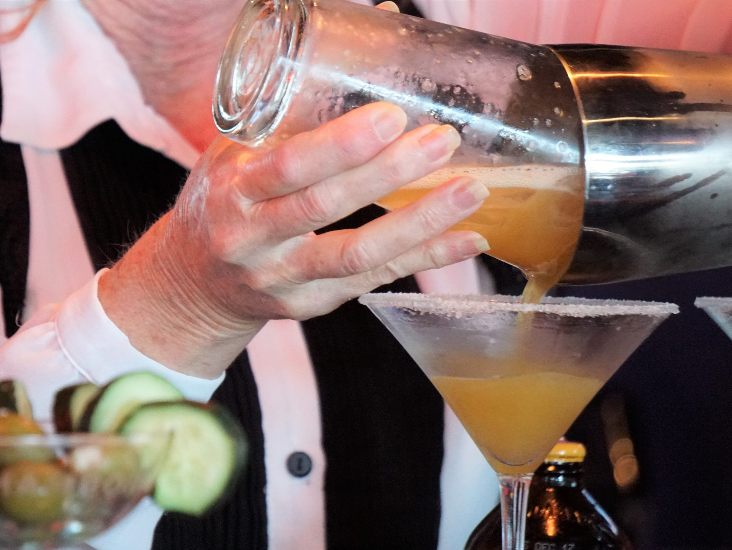 A bartender pours a drink at Latitude 28°02' Restaurant