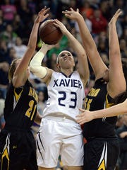 Xavier Hawks forward Rachel Siciliano (23) drives to score against the Hayward Hurricanes defenders Cassidy Preston (21) and Katie Taylor (55) in the D3 WIAA Girls State Basketball tournament at the Resch Center in Green Bay March 13, 2015.