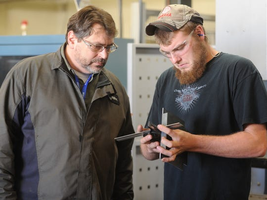 Metals instructor Jeff Beach, left, and student Lukas Griese check the angle on a piece of metal that was bent in a brake press at Moraine Park Technical College in Fond du Lac.