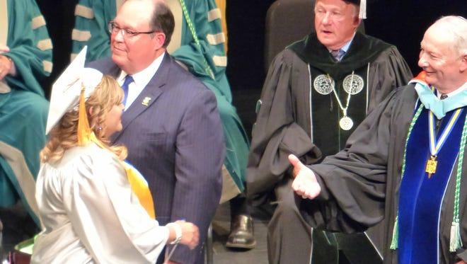 College President Clayton Alred prepares to shake the hands graduate Blanca Zambrano-Rios.