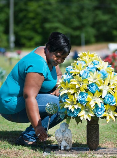 Michelle McCarroll cleans off her brother's grave in Resthaven Memorial Gardens on Wednesday, May 4, 2016.