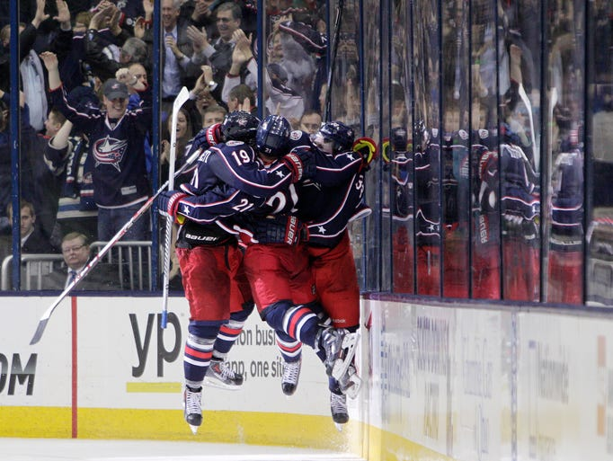 From left, Columbus Blue Jackets' Ryan Johansen, James Wisniewski and Boone Jenner celebrate Johansen's game-winning goal against the Phoenix Coyotes during the overtime period of an NHL hockey game Tuesday, April 8, 2014, in Columbus, Ohio.