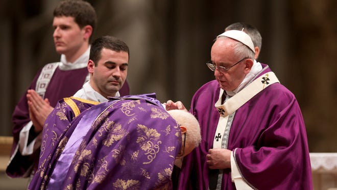 Pope Francis places ashes on the head of a cardinal as he celebrates the Ash Wednesday Mass in St. Peter's Basilica at the Vatican.