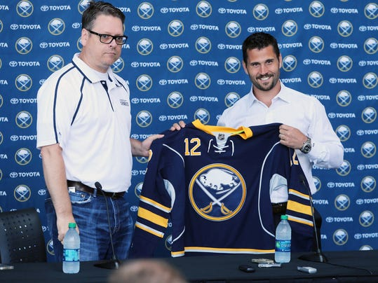 New Buffalo Sabres hockey player Brian Gionta, right, holds a Sabres jersey handed to him by General Manager Tim Murray, left, during a press conference at the First Niagara Center in Buffalo, N.Y., Wednesday, July 2, 2014. (AP Photo/The Buffalo News, Charles Lewis) TV OUT; MAGS OUT; MANDATORY CREDIT; BATAVIA DAILY NEWS OUT; DUNKIRK OBSERVER OUT; JAMESTOWN POST-JOURNAL OUT; LOCKPORT UNION-SUN JOURNAL OUT; NIAGARA GAZETTE OUT; OLEAN TIMES-HERALD OUT; SALAMANCA PRESS OUT; TONAWANDA NEWS OUT