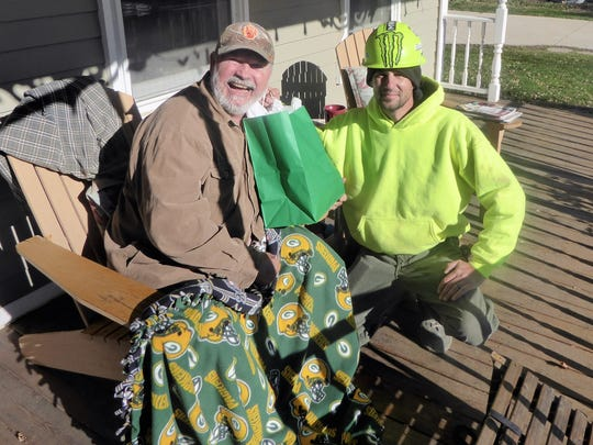 Rich Nowakowski holds a green gift bag given to him by Gary Aide, a mason with Benoy Masonry. About two dozen masons donated an all-expense-paid trip to Green Bay for the Packers game Sunday with Houston to Nowakowski.