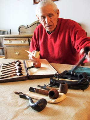 Joe Harb of Coralville displays a small part of his pipe collection, including the seven-pipe, matched-grain set carried by his father-in-law during campaigns in Africa and Europe during World War II. Harb is a nationally recognized reviewer of pipe tobacco blends.