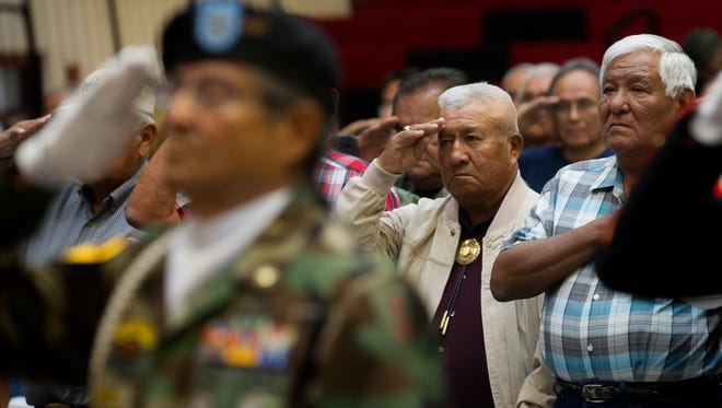 Vietnam Veterans salute during the presentation of colors, Thursday, Sept. 21, 2017 at a Vietnam Veterans Pinning Ceremony at Navajo Technical University in Crownpoint.